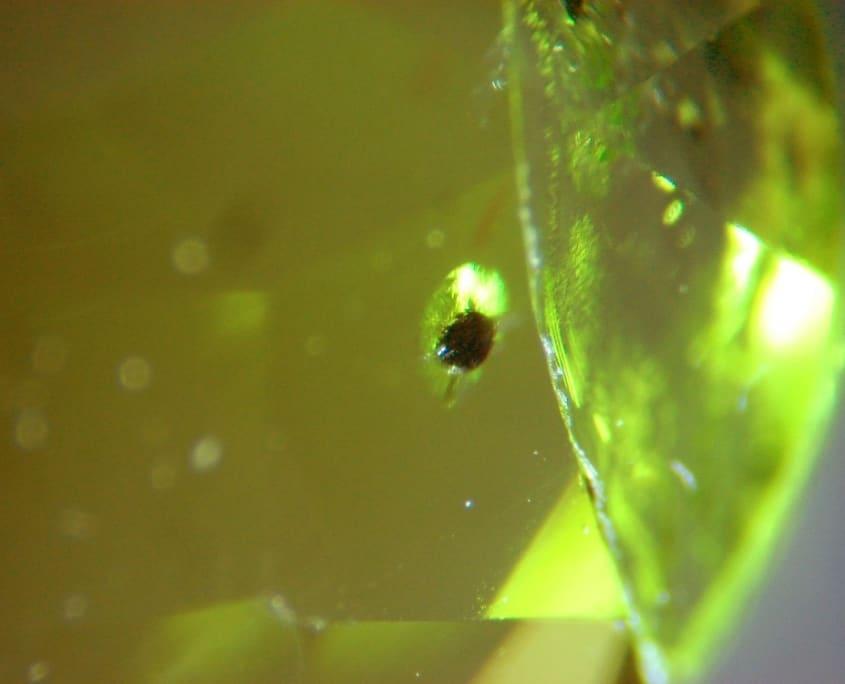 """les inclusions dans les pierres précieuses : cristal de chromite avec halo en """"feuille de nénuphar"""" dans un péridot"""